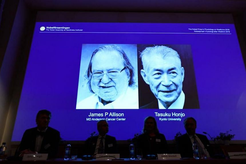 A screen displays portraits of James Allison and Tasuku Honju, winners of the 2018 Nobel Prize in Physiology or Medicine, during a press conference at the Karolinska Institute in Stockholm on Oct 1, 2018.