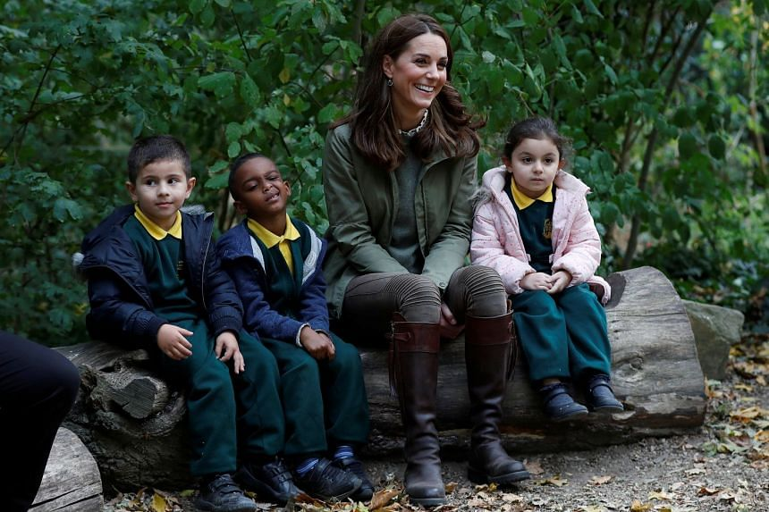 Katherine, Duchess of Cambridge sits on a log with children at Sayers Croft Forest School in London.