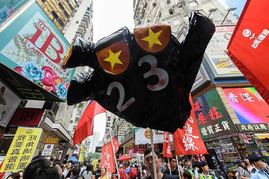 A demonstrator carrying a balloon in the shape of a hand, with the number 23 painted on it in reference to the controversial Article 23 law, during yesterday's protest march in Hong Kong.