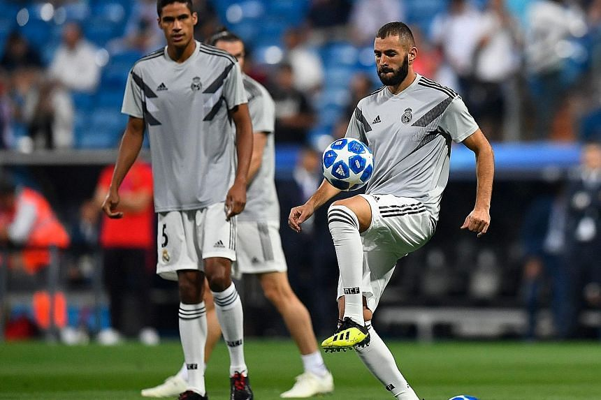 Real Madrid defender Raphael Varane and forward Karim Benzema warming up before their Champions League opener against Roma in Madrid last month. While Varane is set to keep his spot, Benzema's five-game dry spell means he may be replaced by new boy M