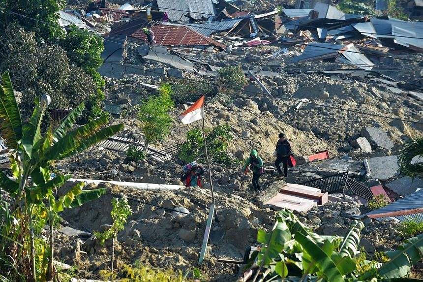 An Indonesian flag fluttering in the midst of damaged homes in Palu, Central Sulawesi, yesterday. The province was hit by a magnitude-6.1 earthquake last Friday afternoon, before a stronger magnitude-7.4 temblor struck, triggering a 7m-high tsunami w
