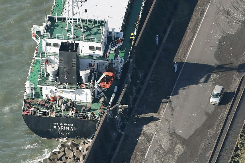 Above: A cargo ship washed ashore by Typhoon Trami in Kawasaki. Left: Trami moved across Japan, lashing the entire country with strong winds.