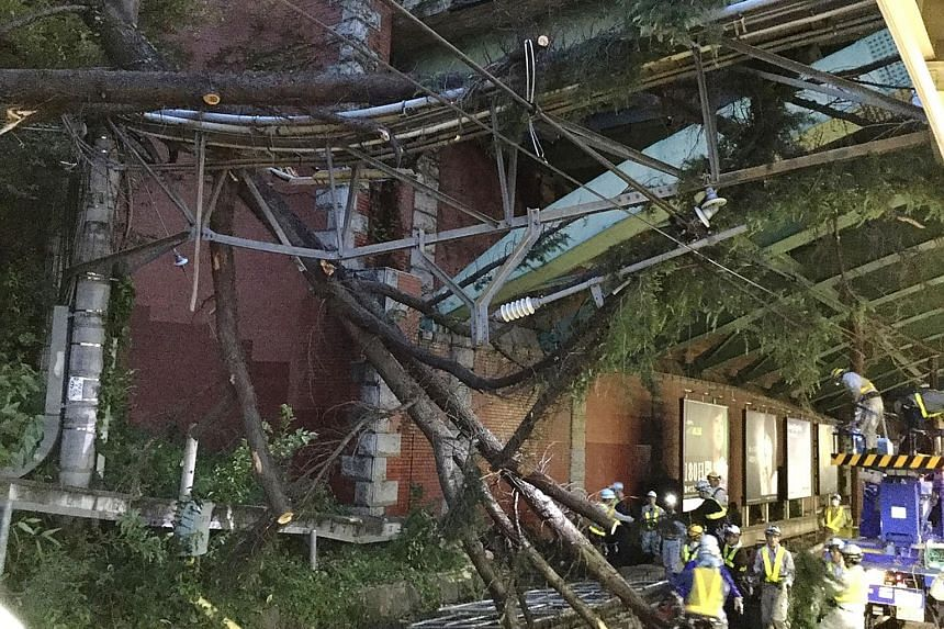 East Japan Railway employees removing fallen branches from Yotsuya station in Tokyo after Typhoon Trami blew through the area overnight.