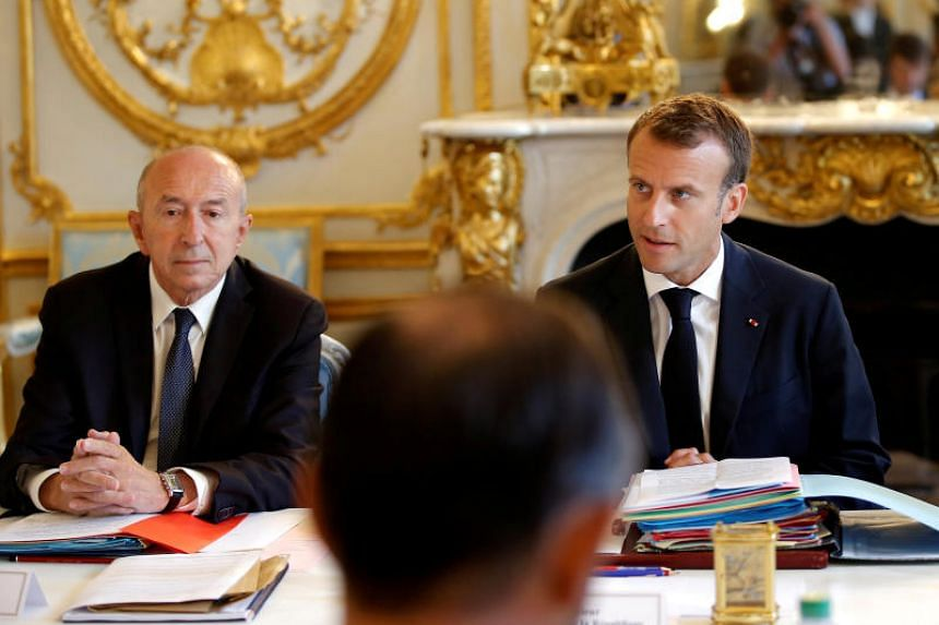 French President Emmanuel Macron sits next to Interior Minister Gerard Collomb (left) as he leads the last cabinet meeting before the government goes on holidays at the Elysee Palace in Paris, France, on Aug 3, 2018.
