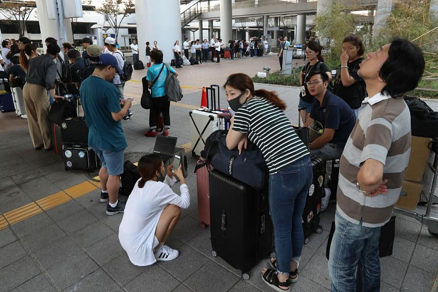 Passengers stranded at the Kansai International Airport due to Typhoon Jebi wait for buses that will transport them from the airport in Izumisano city, Osaka, on Sept 6, 2018.