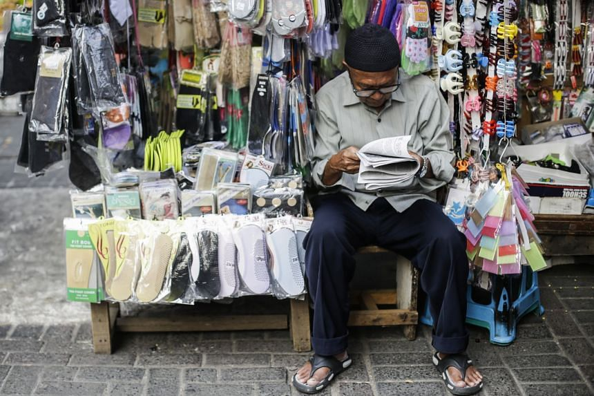 An Indonesian vendor reads a newspaper as he waits for customers at a shopping area in Jakarta, Indonesia, on Sept 26, 2018.