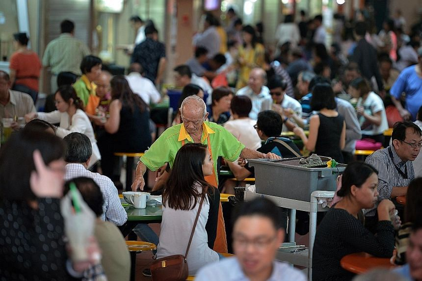 Cleaners at the Maxwell Food Centre. Under the new law, over 40,000 Singaporean and permanent resident cleaners may receive up to 4 per cent more in wages each year.