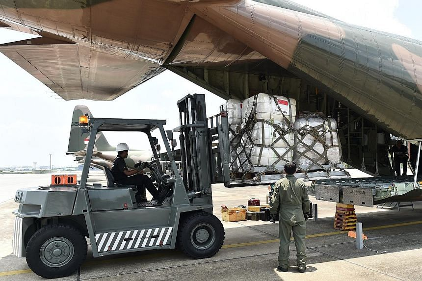 Humanitarian aid supplies being loaded onto a C-130 transport aircraft at Paya Lebar Airbase. Defence Minister Ng Eng Hen said both C-130 aircraft will remain in Sulawesi to transport survivors to other Indonesian cities, as requested by the Indonesi