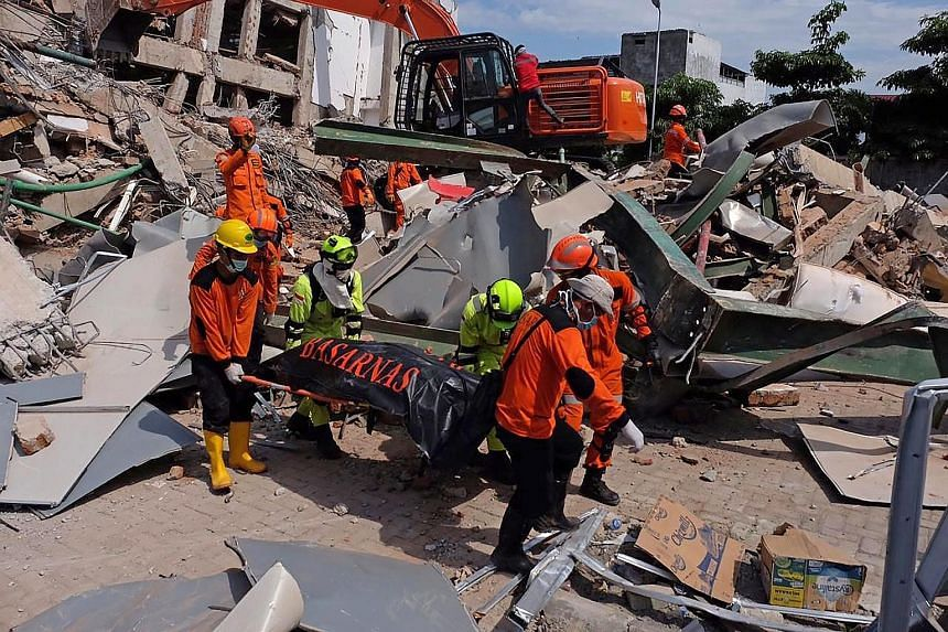Indonesian rescuers removing the body of a quake victim in Palu, in Central Sulawesi, yesterday following last Friday's temblor. Officials said more than 61,000 people have been displaced across the disaster-hit areas.