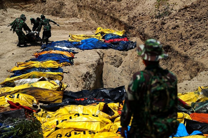 Soldiers moving the bodies of victims of the earthquake and tsunami during a mass burial at the Poboya Cemetery in Palu yesterday. An aerial view of an area devastated by the earthquake in Palu, Central Sulawesi. It is still difficult to reach the mo