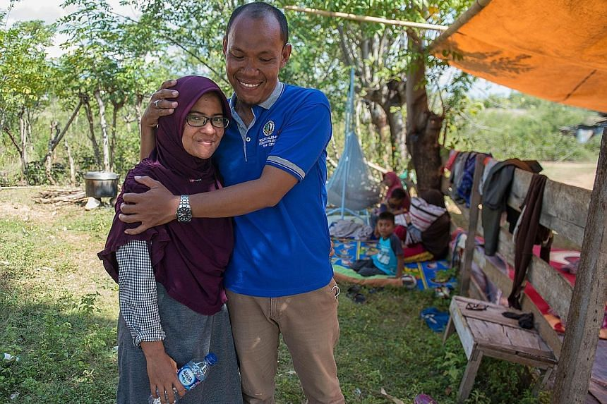 Mr Azwan with his wife Dewi in front of their home and family members in Palu, Central Sulawesi, on Monday, after an earthquake and tsunami hit the area last Friday. He spent two agonising days searching through makeshift morgues and hospitals before