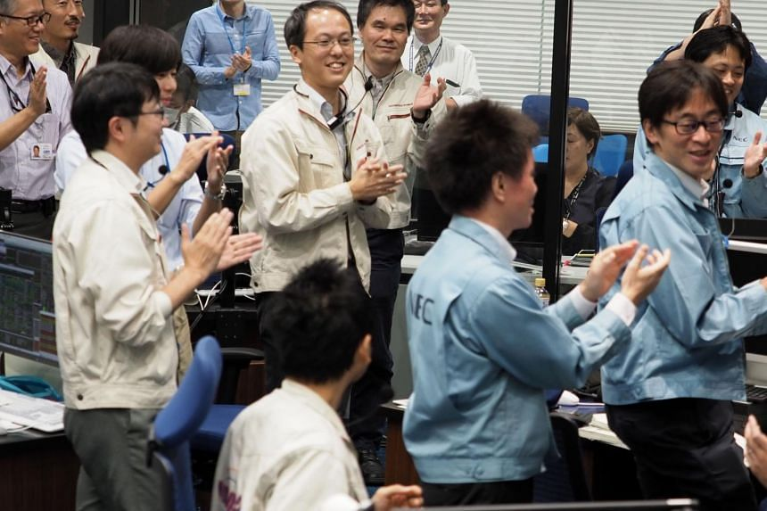 Researchers applaud at a control room in Sagamihara, Kanagawa prefecture, during the French-German Mobile Asteroid Surface Scout deployment operation.