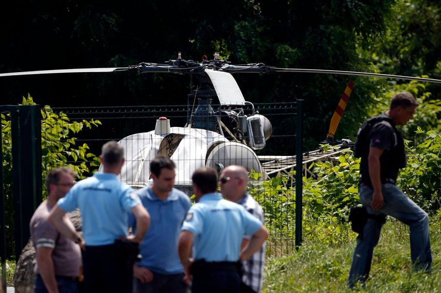French police near a helicopter abandoned by French armed robber Redoine Faid after his escape from prison, on Oct 3, 2018, in Gonesse, France.