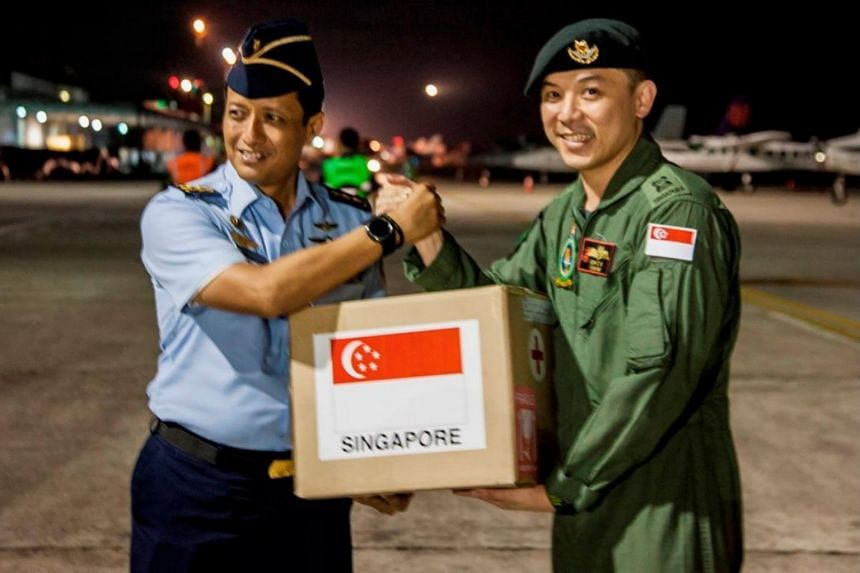 Singapore Armed Forces Mission Commander Oh Chun Keong (right) handing over the relief package to Lt-Col Ali Sudibyo, of the Indonesian Armed Forces at Balikpapan Airport, Indonesia.