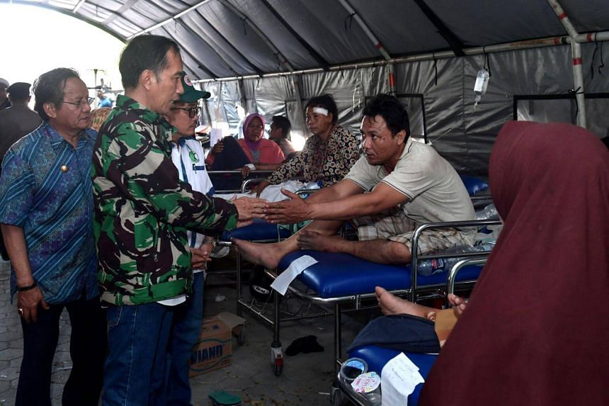 Indonesian President Joko Widodo (second from left), accompanied by Central Sulawesi Governor Longki Djanggola (first from left), visiting people injured by the earthquake and tsunami in Palu, on Sept 30, 2018.