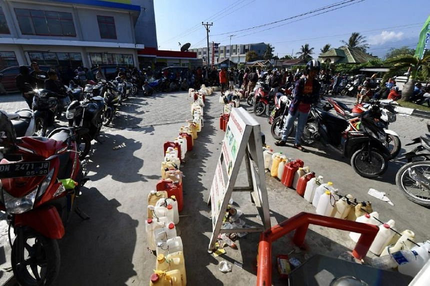 Long queues of people waiting to purchase fuel in Palu.