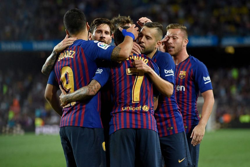 Barcelona players celebrating a goal during a La Liga match against Alaves at the Camp Nou stadium.
