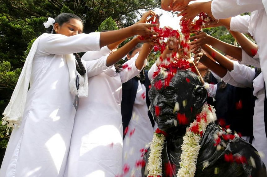 Indian school children's throw flowers over a statue of Mahatma Gandhi as they pay their respects during Gandhi Jayanthi celebration in Bangalore, India, on Oct 2.