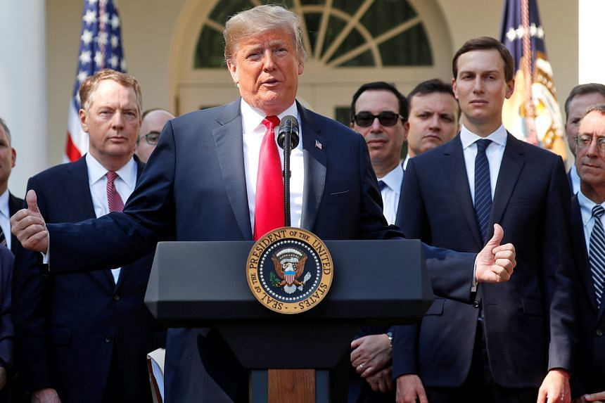 President Donald Trump announcing the new United States-Mexico-Canada Agreement at a news conference in the Rose Garden of the White House on Monday. Flanking him are US Trade Representative Robert Lighthizer (left) and White House senior adviser Jar