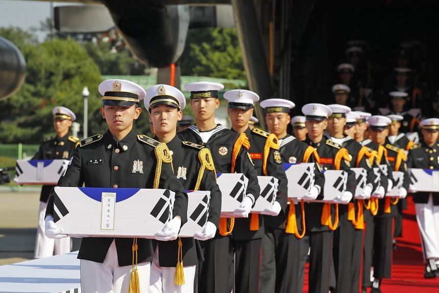 South Korean honour guards with the remains of 64 of the country's soldiers killed in North Korea during the 1950-53 Korean War. The remains were found during a joint excavation project between the United States and North Korea.