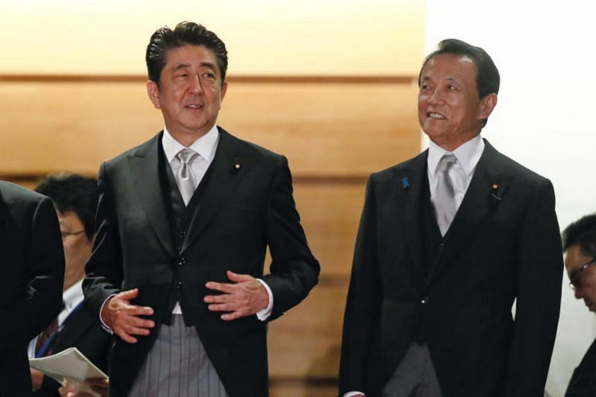 (From left) Japan's Prime Minister Shinzo Abe talks with Finance Minister Taro Aso at the prime minister's official residence in Tokyo, on Oct 2, 2018.