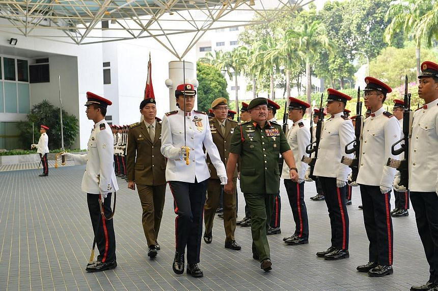 Above: Malaysia's Deputy Minister for Defence Liew Chin Tong (left) meeting Defence Minister Ng Eng Hen at the Ministry of Defence yesterday. Right: General Tan Sri Zulkifli Zainal Abidin reviewing the guard of honour at Mindef yesterday.