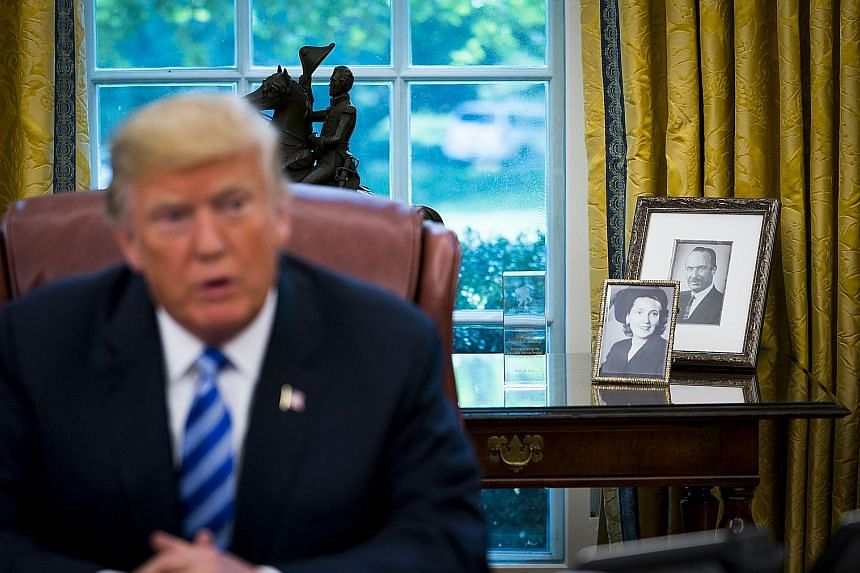 President Donald Trump claims he had almost no financial help from his parents, whose photos are in the background, but a New York Times investigation revealed he received the current equivalent of at least US$413 million.