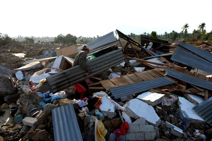 A resident tries to salvage his collapsed home in the village of Petobo in Palu, on Oct 3, 2018.