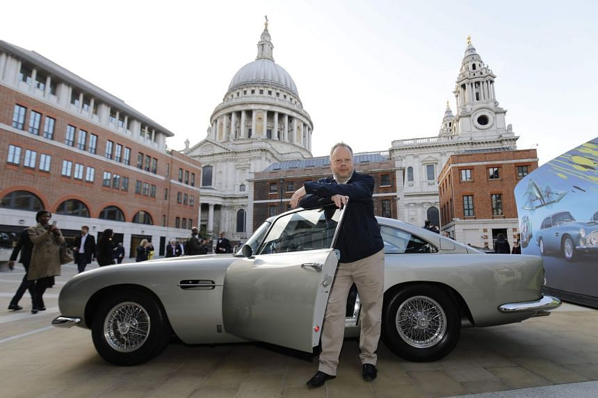 CEO Andy Palmer posing next to Aston Martin cars as the company is floated in London.