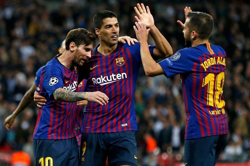 Lionel Messi (left) celebrates scoring his team's fourth goal, his second, with Luis Suarez (centre) and Jordi Alba.