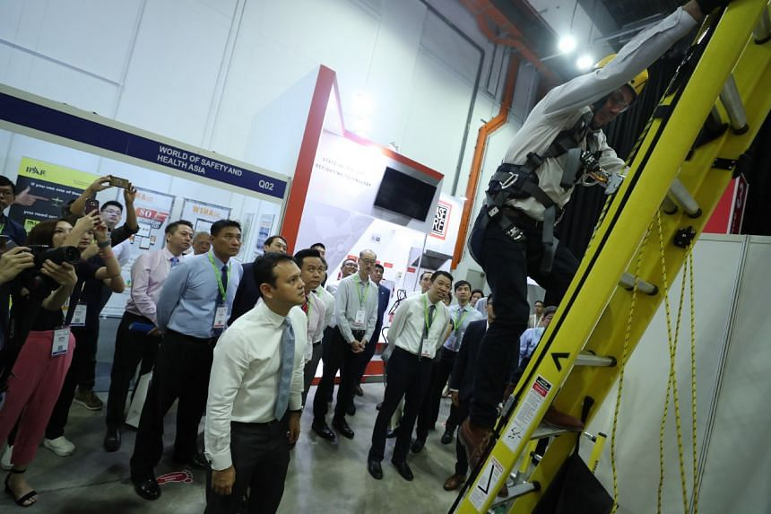 Mr Zaqy Mohamad viewing a demonstration of a fall control ladder system. ST PHOTO: TIMOTHY DAVID