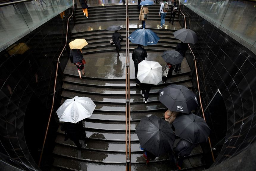 Office workers are seen during wet weather in Sydney, on Oct 4, 2018.