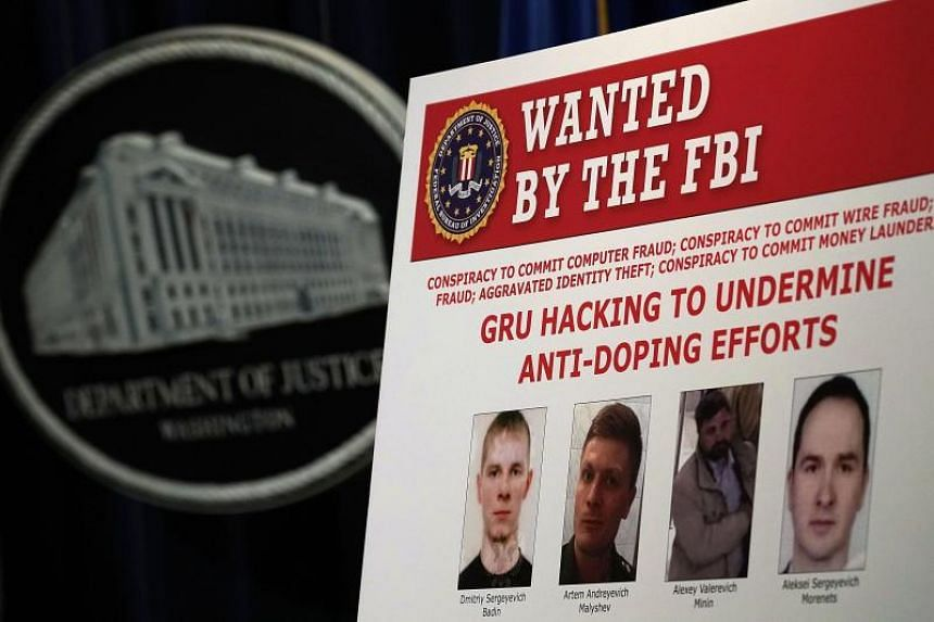 """A """"wanted"""" poster of Russian individuals is seen during a news conference to announce criminal charges in Washington on Oct 4, 2018."""