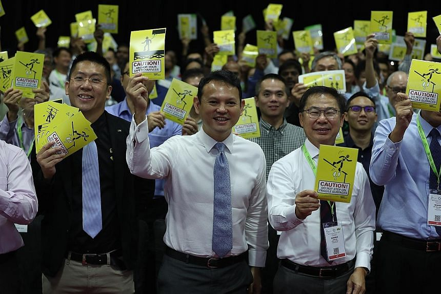 Minister of State for Manpower Zaqy Mohamad, flanked by the International Powered Access Federation's South-east Asia regional general manager Raymond Wat (left) and Workplace Safety and Health Council chairman John Ng, holding up stickers containing