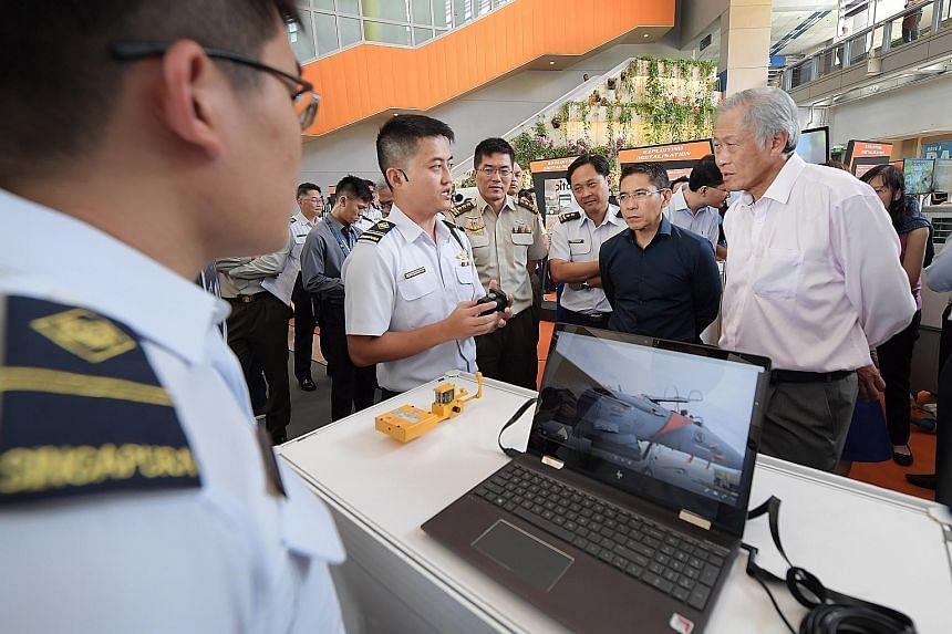 Military Expert 4 Sebastian Zheng briefing Defence Minister Ng Eng Hen on his team's project, which allows the Republic of Singapore Air Force to calibrate its navigation compass for the F-15SG aircraft without the need for a certified physical compa