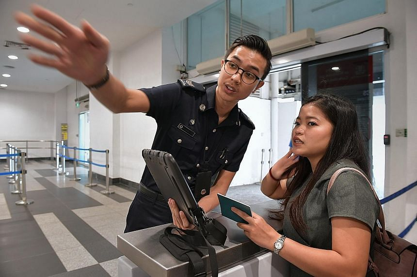 Indonesian tourist Indah, 21, receives help from an officer of the Immigration and Checkpoints Authority (ICA), Sergeant Muhammad Fazril, on using an electronic arrival card instead of the paper disembarkation/embarkation card to provide her personal