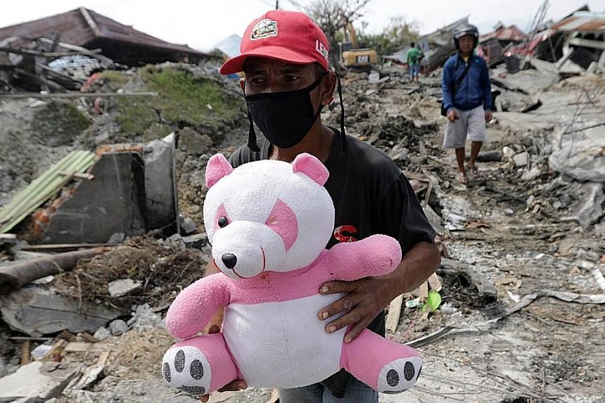 A man holding a teddy bear in disaster-hit Petobo village in Palu, Central Sulawesi, yesterday. The village was destroyed by mud from a landslide triggered by strong quakes. Hundreds of locals trying to flee Palu were stranded at the airport. There i