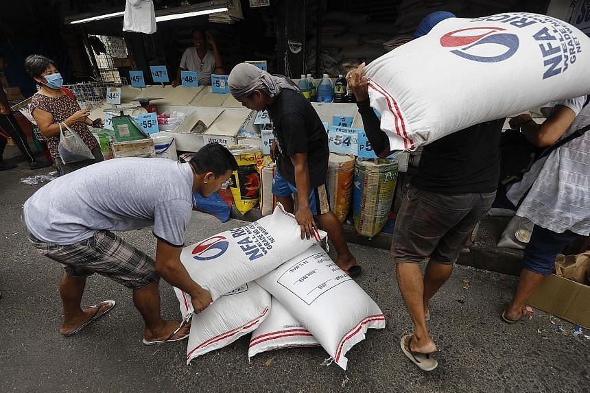 Filipino workers carrying sacks of rice into a store in Quezon City. The consumer price spike began at the start of the year following tax increases on fuel, sugary drinks and cigarettes - then swiftly moved to rice.
