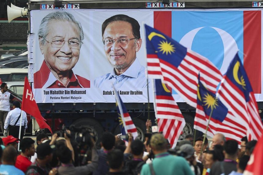 A lorry with banners of Malaysian Prime Minister Mahathir Mohamad (left) and Malaysia's prime minister-in-waiting Anwar Ibrahim during nomination day for the by-election in Port Dickson on Sept 29, 2018.