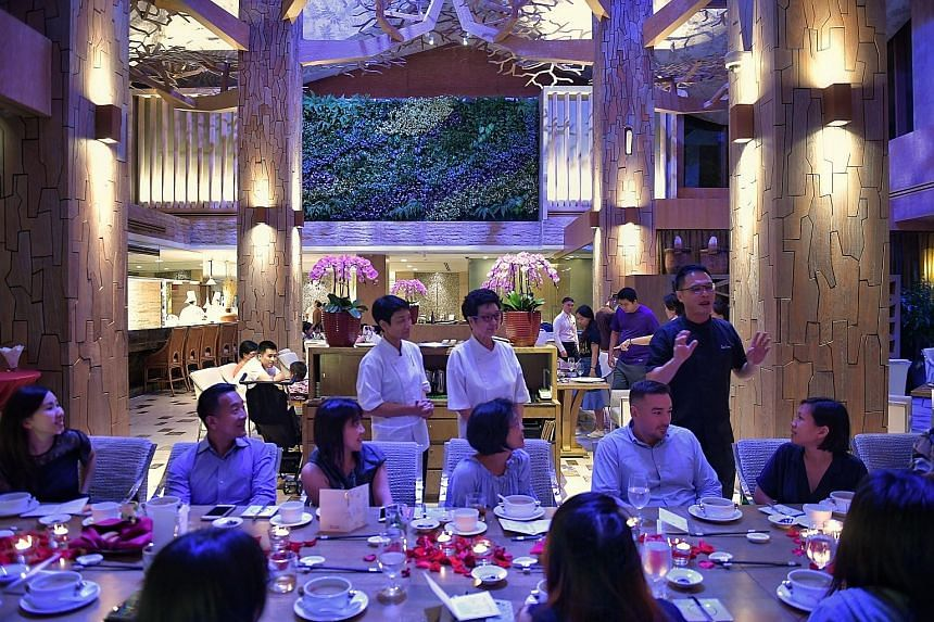 Chef Sam Leong (standing, right) with ST readers at his restaurant Forest, as they are treated to a meal created by him, his mother, Madam Pit Yoke Eng (standing, centre), his wife, Forest (standing, left), and his son, Joe.