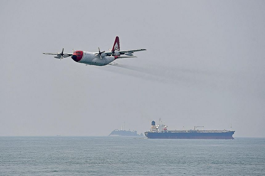 """The exercise scenario also required the immediate evacuation of an """"injured"""" crew member on board the damaged tanker. The spill response teams sprayed dispersants from a C-130 aircraft to contain a mock oil spill during the exercise yesterday."""