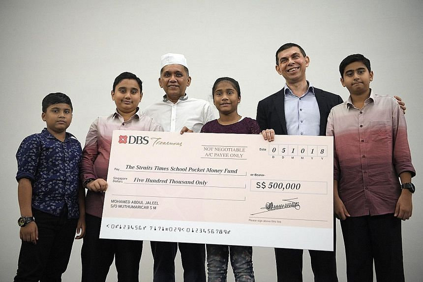 Mini Environment Service Group founder and chief executive Mohamed Abdul Jaleel (in white) with his grandchildren (from left) Mohamed Ayman, 11; Mohamed Shayaan, 11; Ayana, 11; and Mohamed Rayhan, 12, as he presented the fund's chairman, Mr Warren Fe