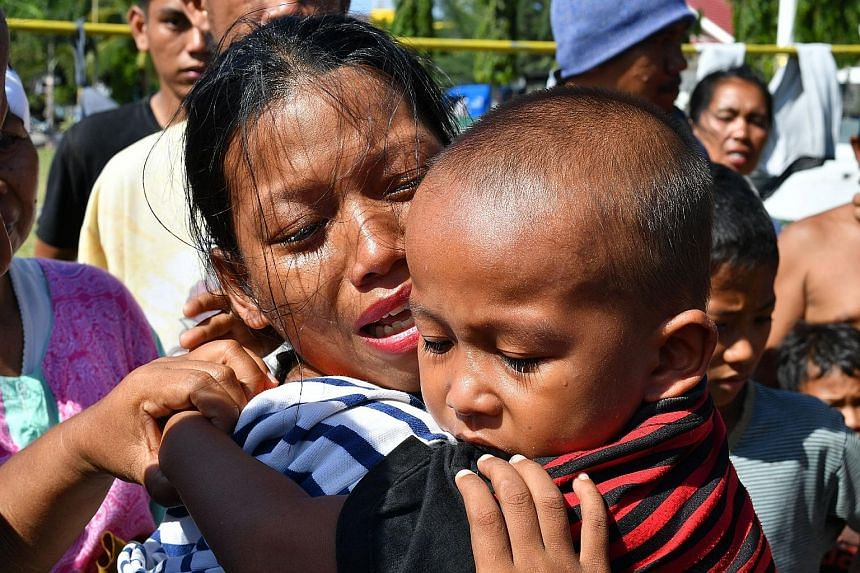 Indonesian military personnel unloading supplies from a Singapore military plane at Mutiara Al Jufri Airport in Palu yesterday. Ms Susi Rahmatia in an emotional reunion with her five-year-old son Jumadil yesterday, after he went missing for seven day
