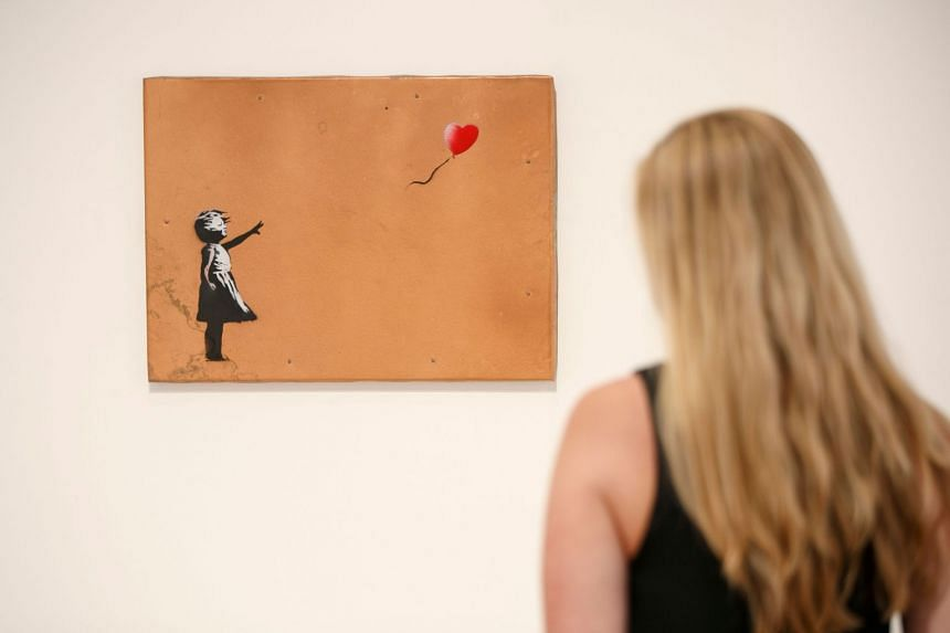 """Immediately after """"Girl With Balloon"""" had been sold to a phone bidder for £1.04 million (S$2.5 million), part of the painting was mysteriously shredded, according to Sotheby's."""
