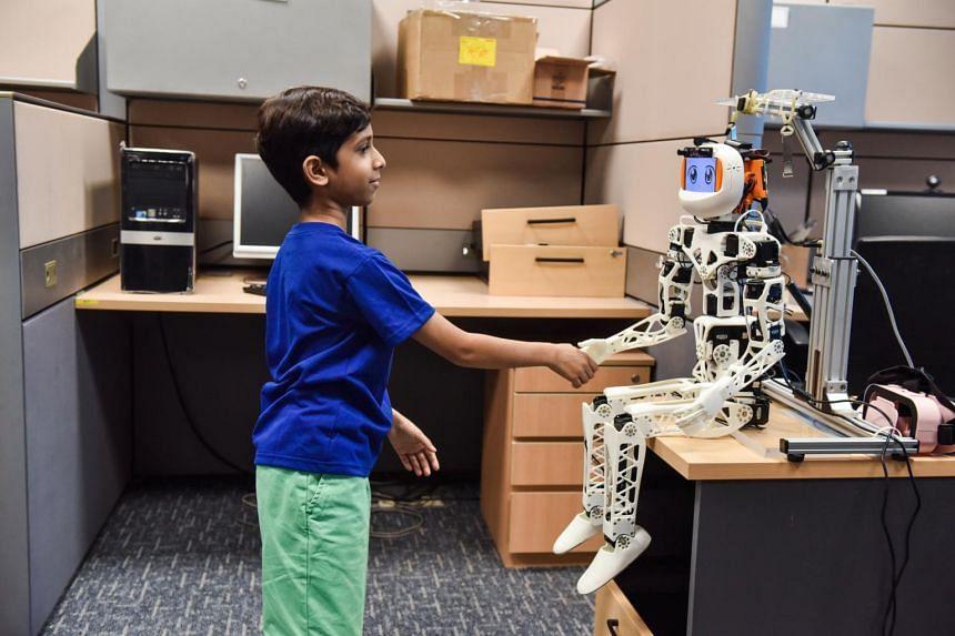 Zahaan Tambawala shakes hands with Poppy, a customisable robot.
