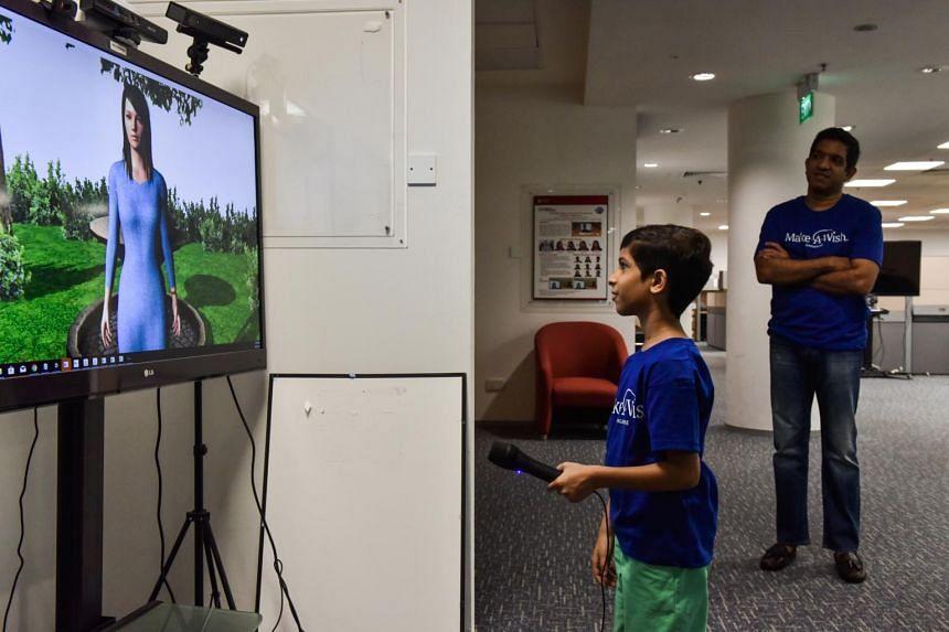 Zahaan Tambawala interacting with virtual human Nicole while his father, Mr Murtuza Tambawala, looks on.