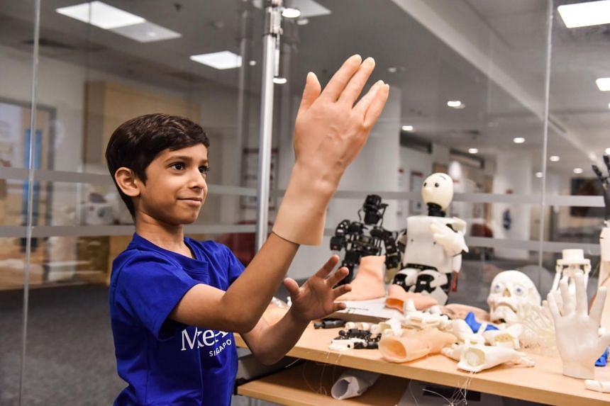 Zahaan Tambawala tries on artificial skin designed for robots during a tour of a robotics laboratory at the Institute for Media Innovation at Nanyang Technological University.