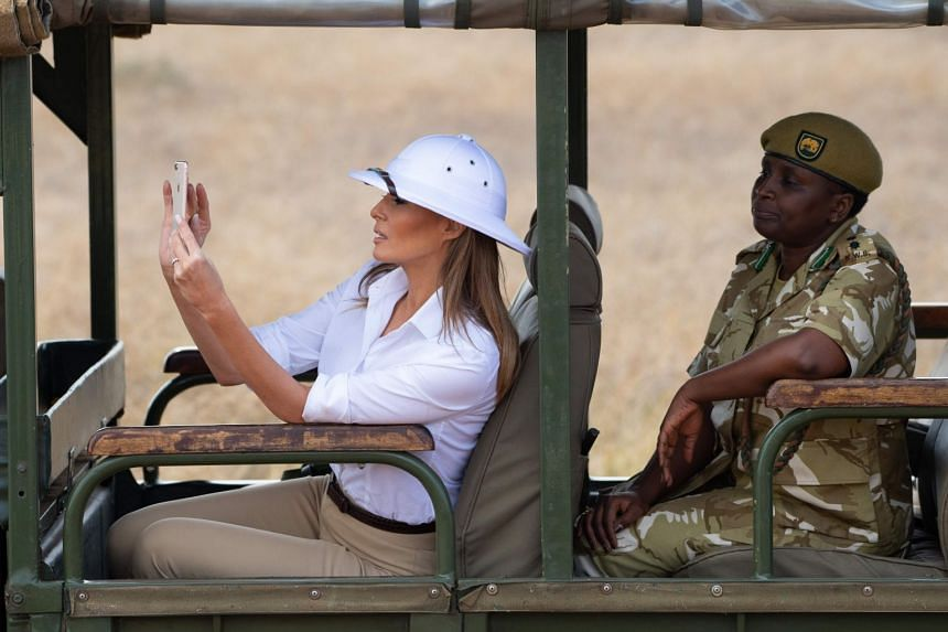 As the first lady sat alone in her vehicle, peering through binoculars and shooting photos of zebras, giraffes and impalas on her iPhone, critics were parsing her decision to wear the attention-grabbing white hat.