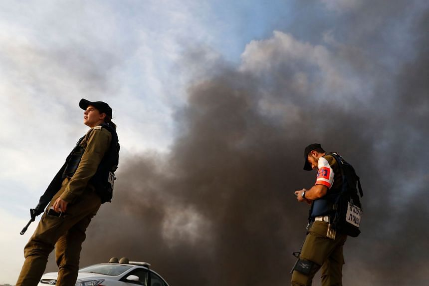 A picture taken from the southern Israeli kibbutz of Nahal Oz across the border with the Gaza Strip shows Israeli forces standing as smoke rises from burning tyres during a Palestinian demonstration on Oct 5, 2018.
