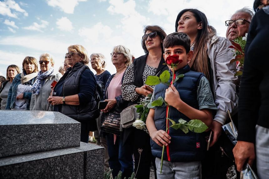 People gather to pay tribute to the late French-Armenian singer Charles Aznavour after his funeral ceremony, in front of his grave.